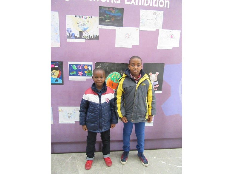 Otlotleng (right) with his brother Tshenolo in front of his artwork