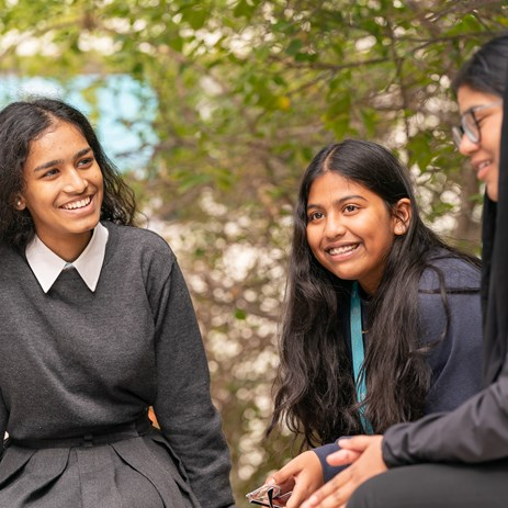 3 secondary girls talking outside beneath a tree