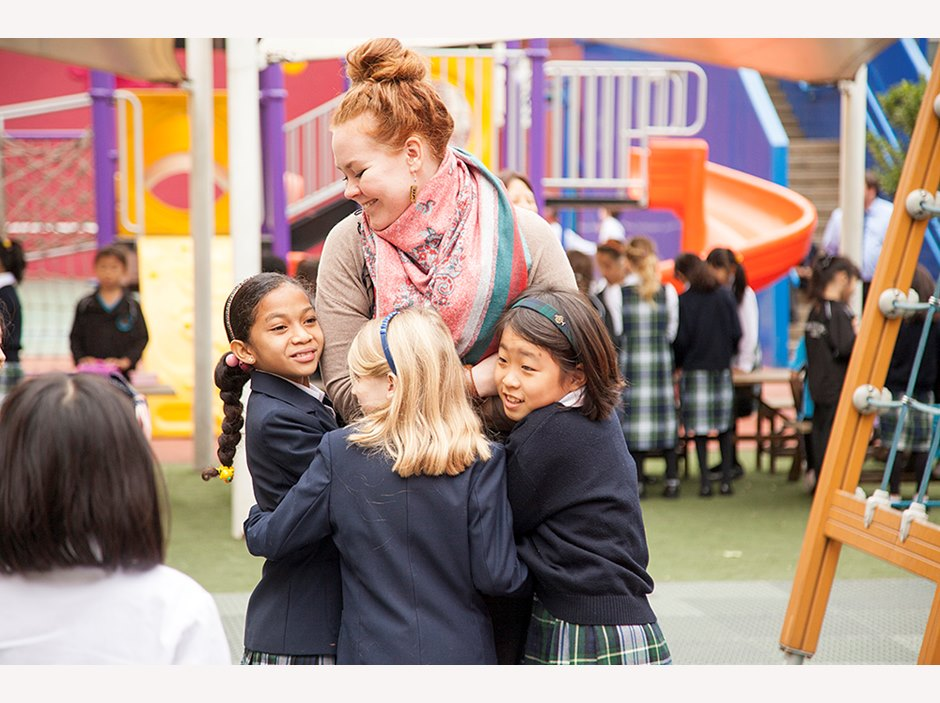 Three students hugging their teacher during playtime in the Primary Campus playground.