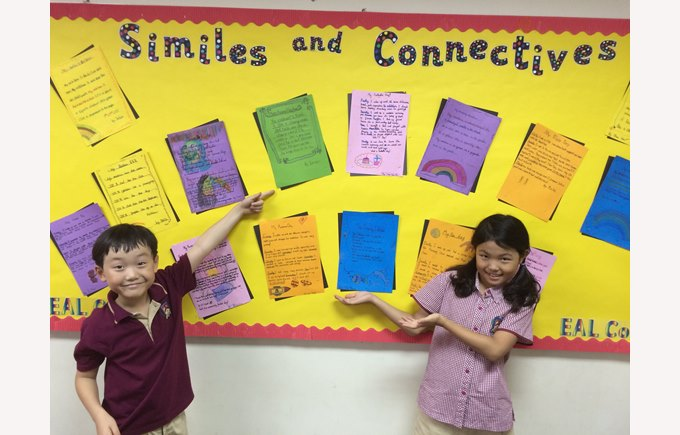 Two students showcasing a display board at Primary for EAL