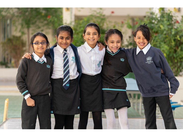 Five young girls stand outside, smiling, wearing their school uniforms