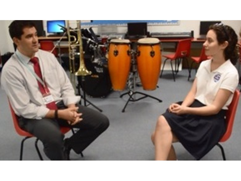 Girl interviewing teacher in a music room
