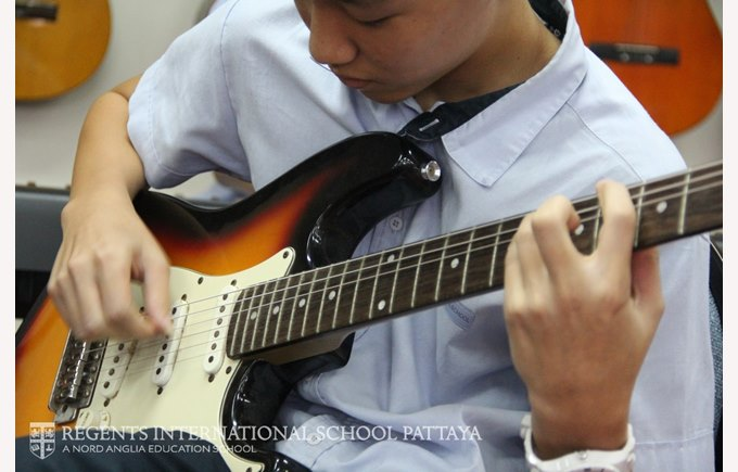 Student playing electric guitar.