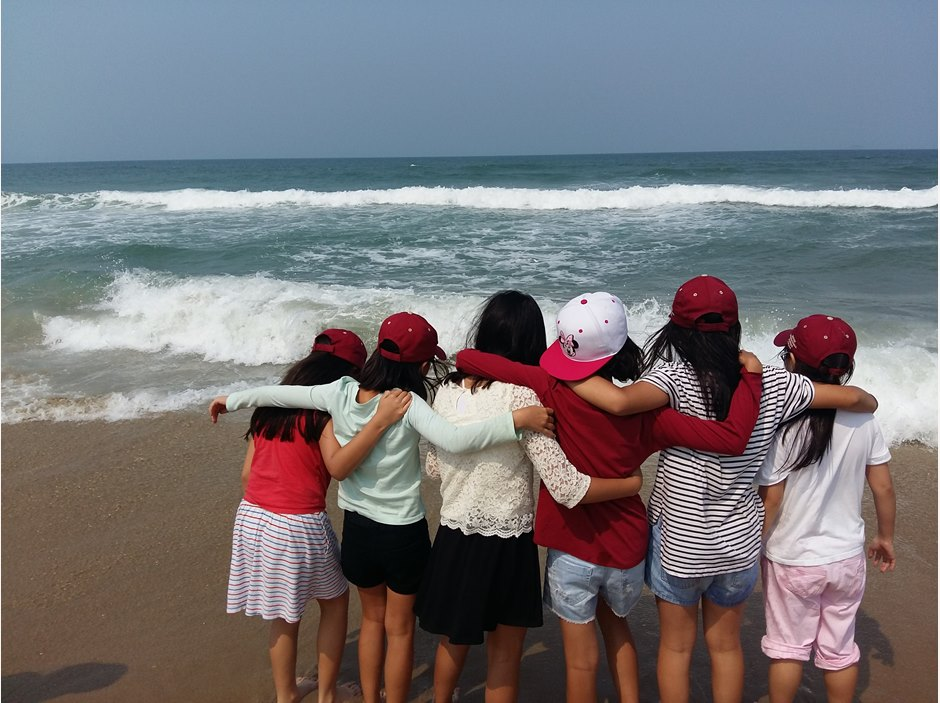 Six girls with arms around each other at the beach