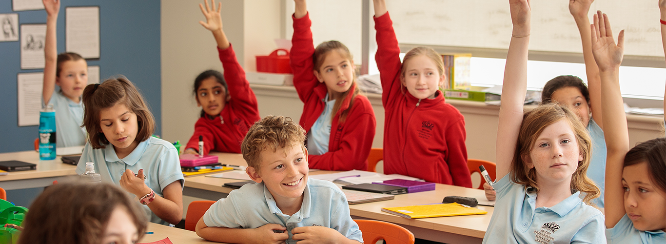 Children raise their hands to answer a question in the classroom.