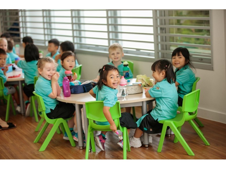 Kindergarten children eating lunch around a table