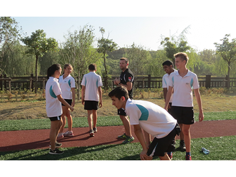 PE Teacher Jonathan Fudge with his students in an athletics class