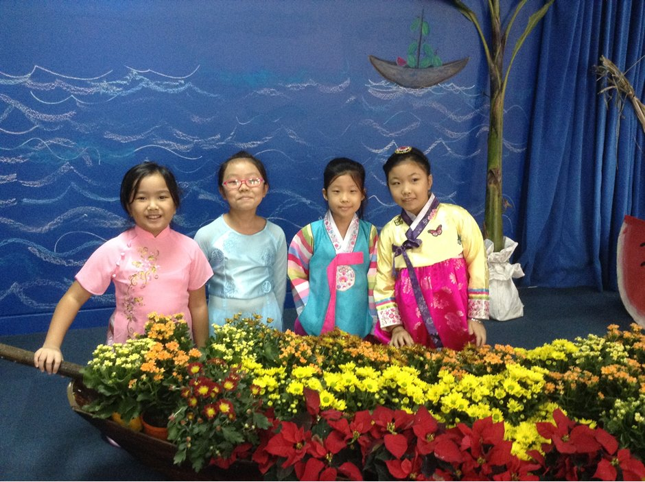 Students standing behind flower boat