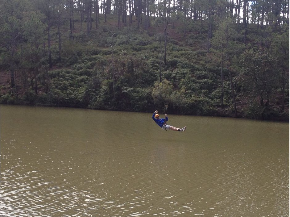zip-lining student across the lake in Dalat