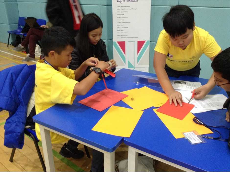 Four students cutting paper and folding