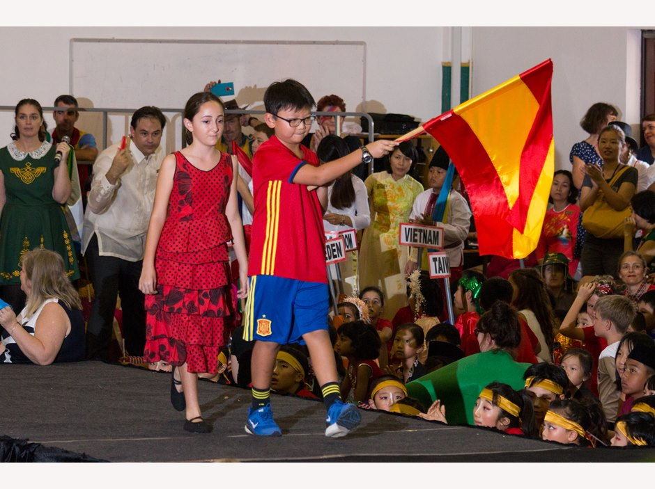 A boy holding Spain flag parading in AP1 International Week Assembly
