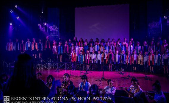 Primary and Secondary choirs and orchestra on stage at Regents International School Pattaya