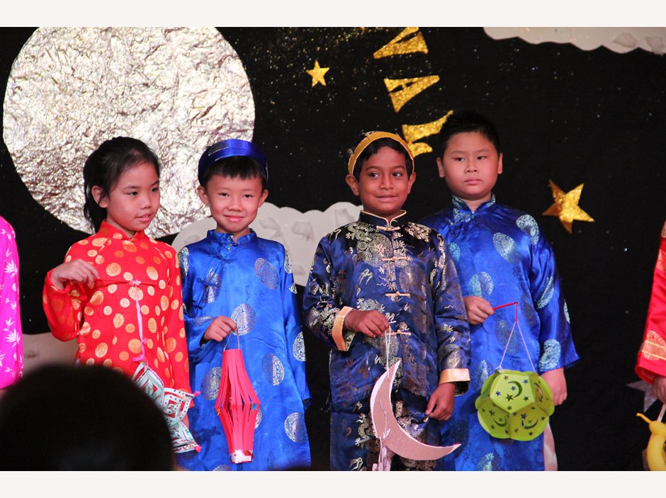 Four students holding lanterns in TX Moon Festival Assembly