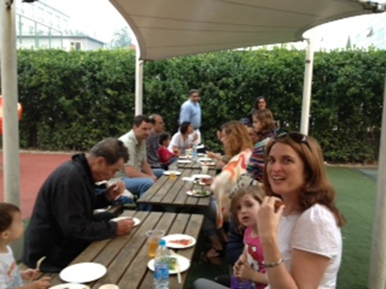 Families enjoying food and drinks at the long tables.