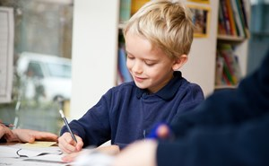 Primary student working with pencil and paper at a desk