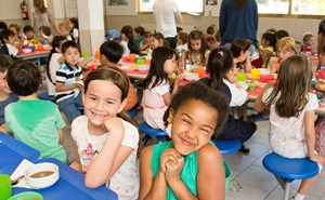 Two primary school girls smiling at the camera in the cafeteria