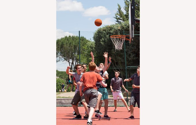 A group of secondary school boys play basketball outside