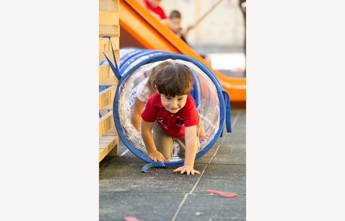 Kindergarten pupil crawls through a tunnel in the playground