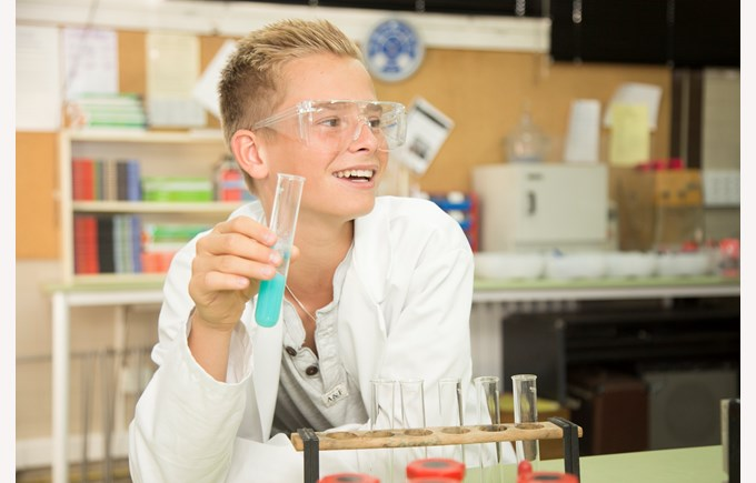 A secondary school pupils holding a test tube and smiling in a science lesson