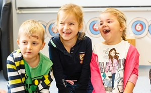 Three Early Years children laughing