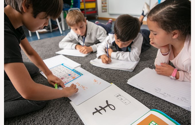 Young students learning to write in a new alphabet