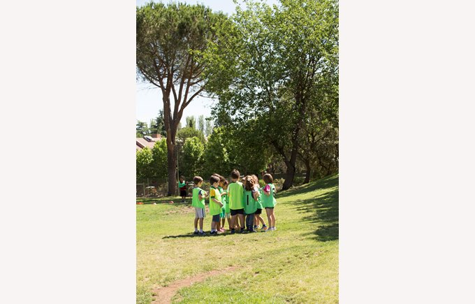 A group of primary school children huddle on the school field in gym class