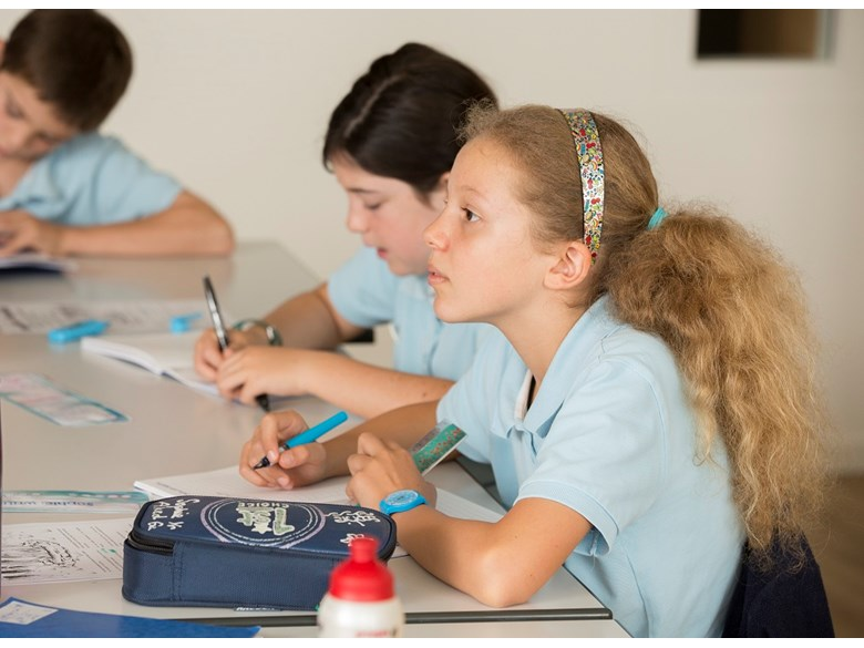 The image shows two girls sitting at their school desks