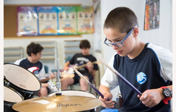 A grade 7 boy in his school uniform playing the drums