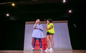 Girls acting play practice on stage with lights
