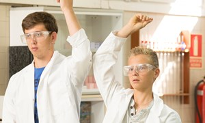 Two secondary school boys put their hand up in a science lesson
