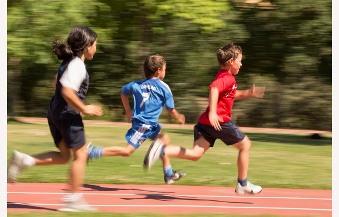 Primary schoolchildren sprinting round the athletics track