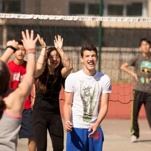 A secondary school pupil laughs as he plays volleyball outside