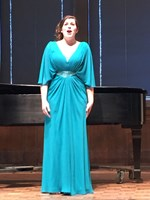woman singing on stage in a blue dress in front of a piano