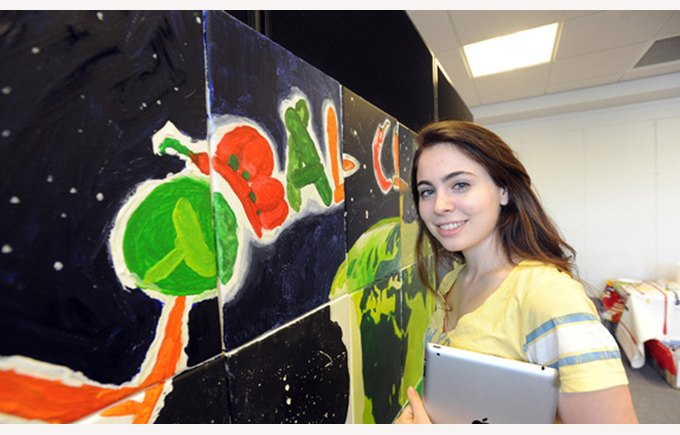 Student with iPad next to Global Classroom picture