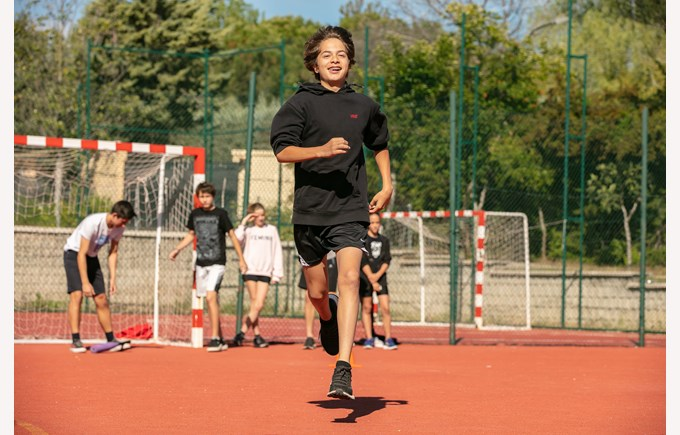 ICS Secondary student running on the court