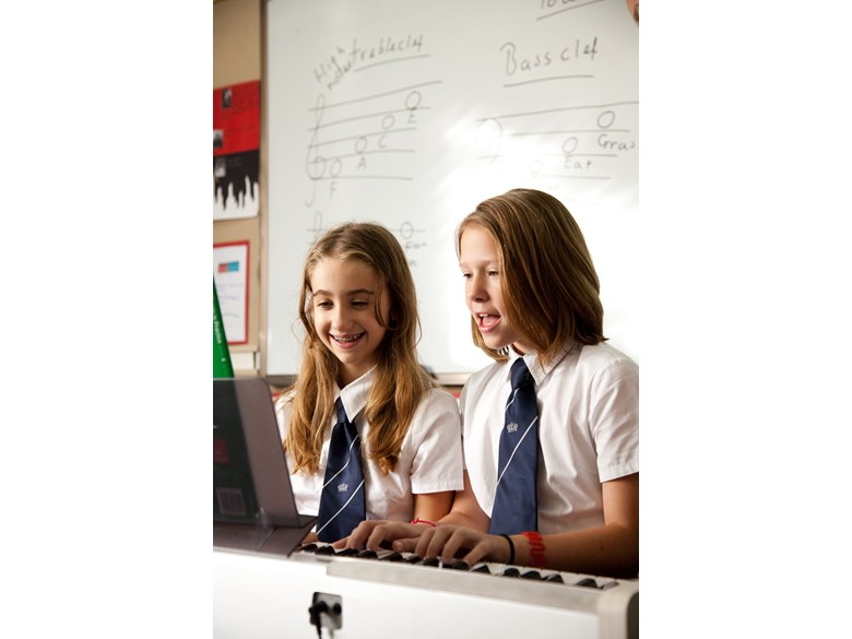 NAE students playing on piano