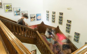 Blurred students going up and down wooden stairs in school