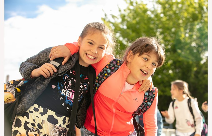 A pair of girls hug each other with their backpacks on