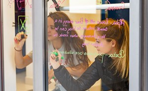 Student writing on glass wall