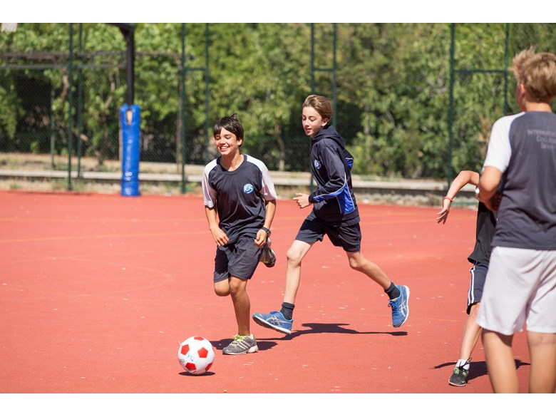 Grade 6 boys playing football outside on the court