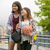 Two girls at ICS with a basketball and lunchbox