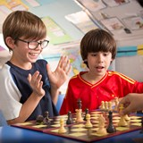 Two primary school boys playing chess and one clapping his hands in enjoyment