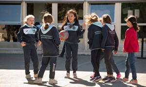 Primary playground girls playing basketball recess break windy February Denis Doyle