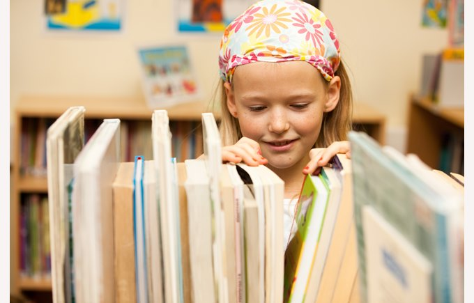 Young student, pupil choosing a book in the library