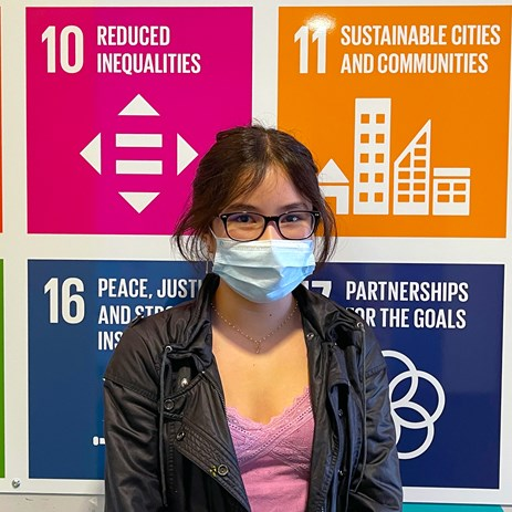 Student standing in front of the Global Goals