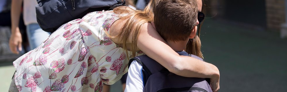 A primary school student being embraced by his mother at the end of the day
