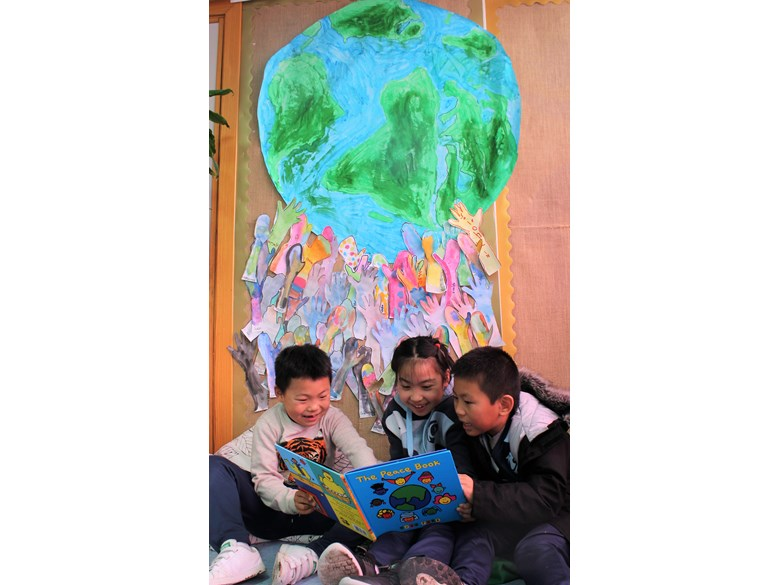 World Children's Day 2019 ICS Primary students reading with collaborative mural