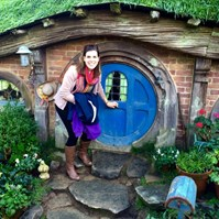 Women travelling New Zealand in front of hobbit house