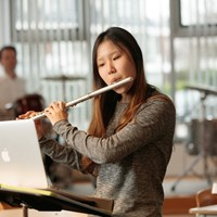 Student plays flute during music lesson