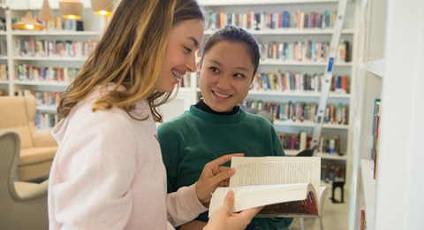 Secondary library English post students sharing a book smiling